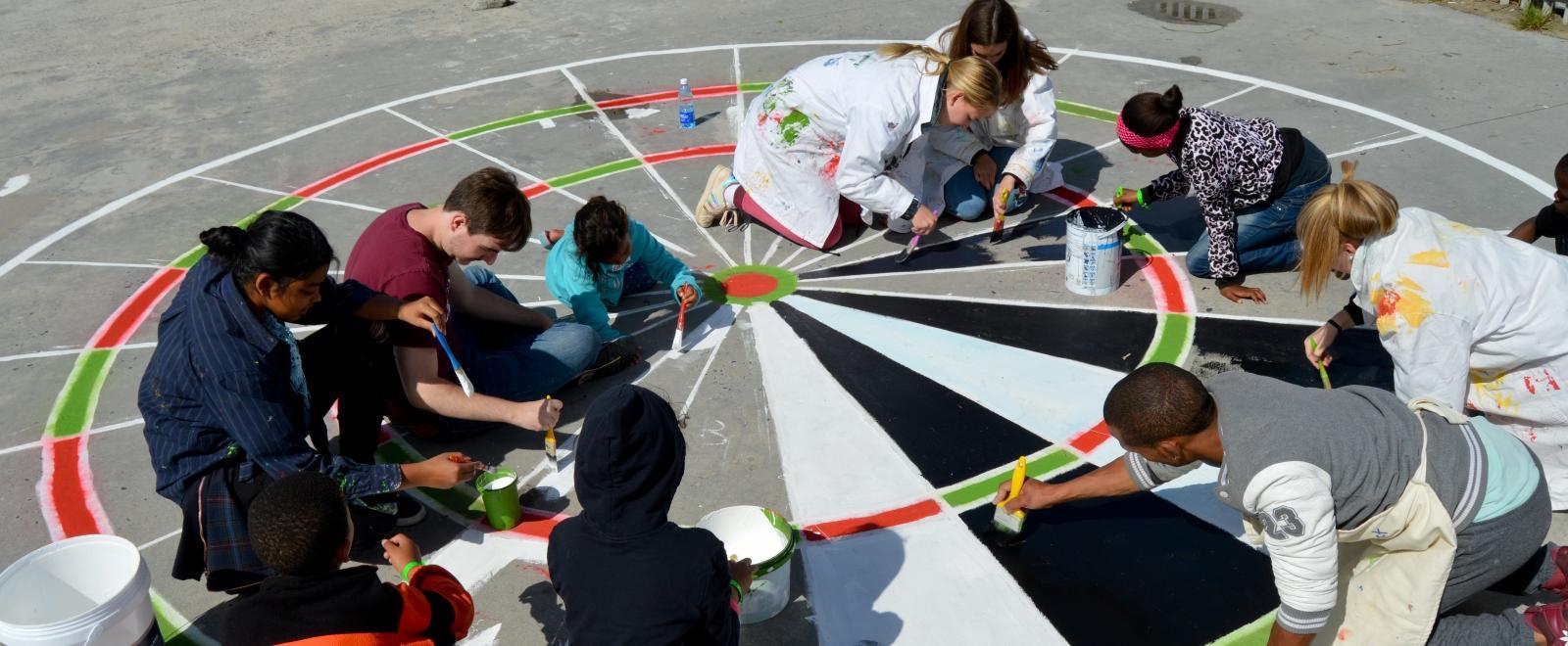Un groupe de Roundsquare accueilli par la Tore's Foundation peint une aire de jeux avec les membres des communautés locales au Cap, Afrique du Sud.